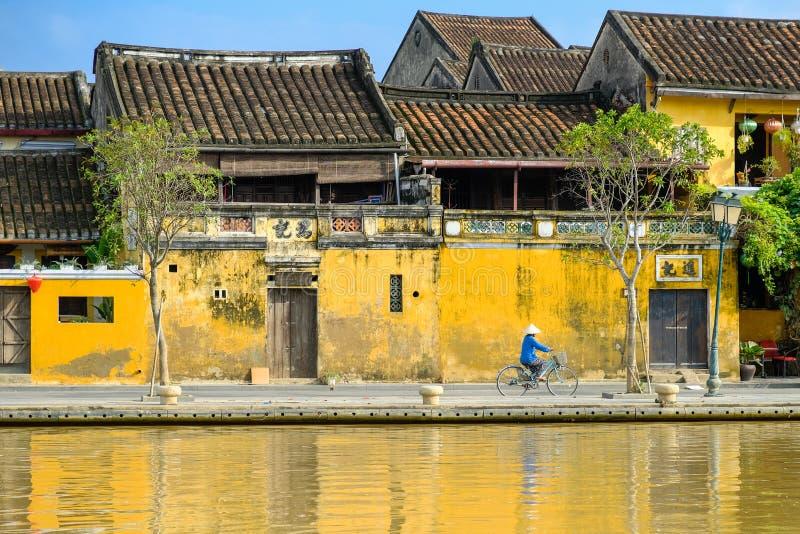 Hoi An/Vietnam, 12/11/2017: Lokale Vietnamese vrouw met rijsthoed op een fiets die voor traditionele huizen overgaan met stock afbeelding