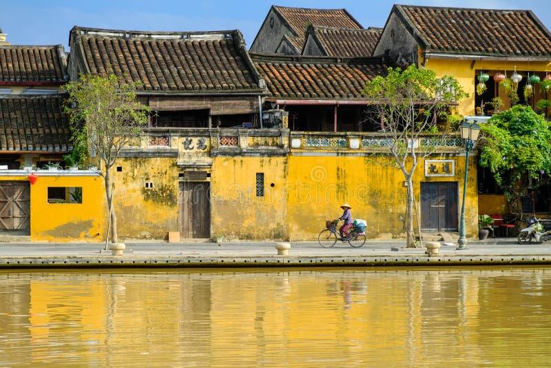 Hoi An/Vietnam, 12/11/2017: Lokale Vietnamese vrouw met rijsthoed op een fiets die voor traditionele huizen overgaan met royalty-vrije stock afbeelding