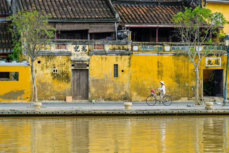 Hoi An/Vietnam, 12/11/2017: Lokale Vietnamese vrouw met rijsthoed op een fiets die voor traditionele huizen overgaan met royalty-vrije stock afbeeldingen