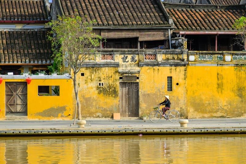 Hoi An/Vietnam, 12/11/2017: Lokale Vietnamese vrouw met rijsthoed op een fiets die voor traditionele huizen overgaan met stock foto