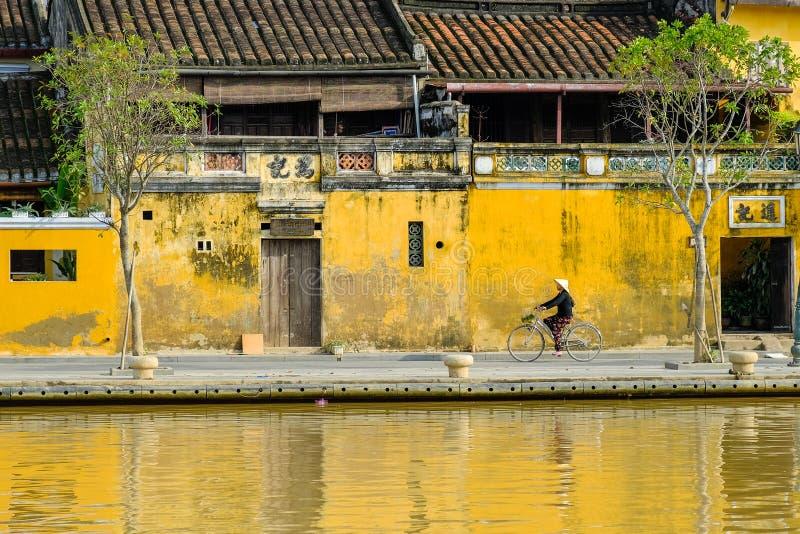 Hoi An/Vietnam, 12/11/2017: Lokale Vietnamese vrouw met rijsthoed op een fiets die voor traditionele huizen overgaan met royalty-vrije stock foto's