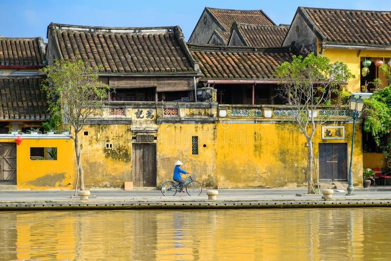 Hoi An/Vietnam, 12/11/2017: Lokale Vietnamese vrouw met rijsthoed op een fiets die voor traditionele huizen overgaan met stock foto's