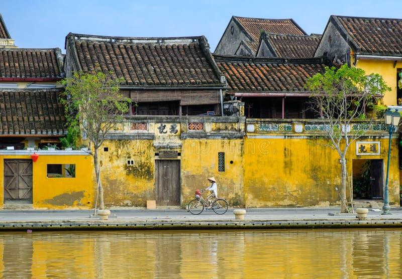 Hoi An/Vietnam, 12/11/2017: Lokale Vietnamese vrouw met rijsthoed op een fiets die voor traditionele huizen overgaan met royalty-vrije stock fotografie