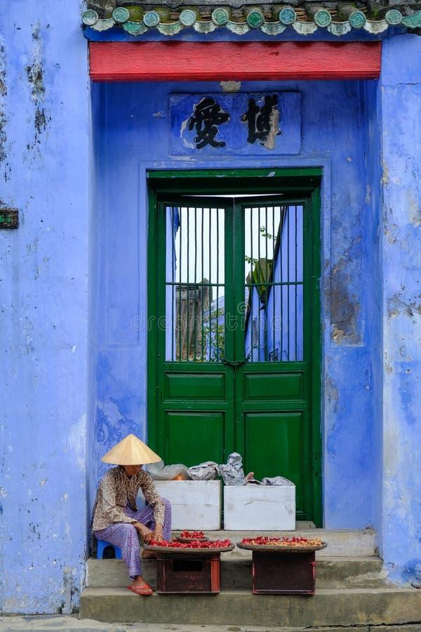 Hoi An/Vietnam, 12/11/2017: Lokale Vietnamese vrouwenzitting voor een traditionele huisingang met blauwe muren en het verkopen stock afbeeldingen
