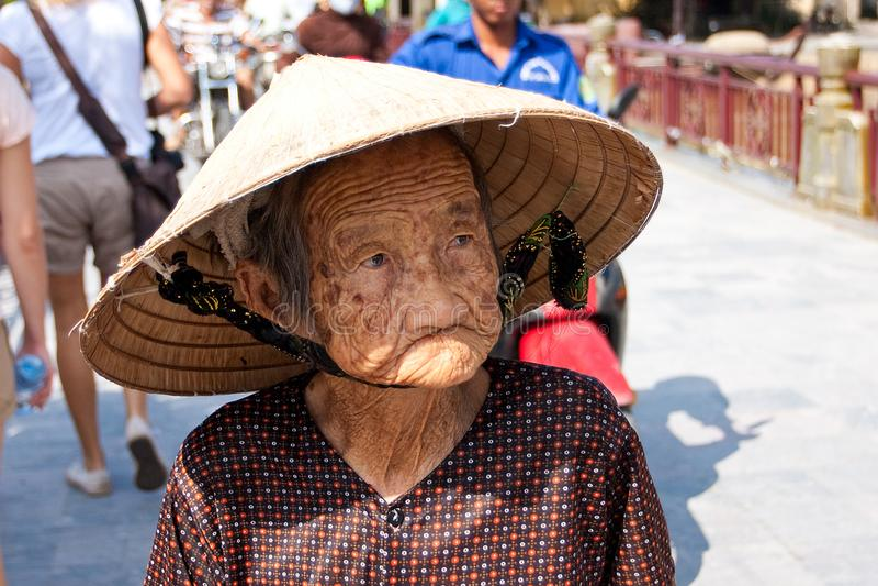 Hoi An, Vietnam - NOVEMBER 02, 2011: Een bejaarde Vietnamese vrouw in een traditionele strohoed royalty-vrije stock afbeeldingen