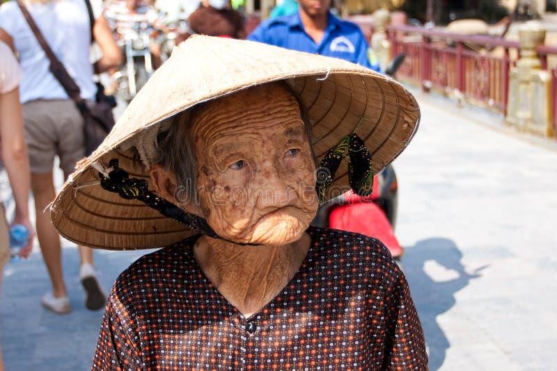 Hoi An Vietnam - NOVEMBER 02, 2011: En äldre vietnamesisk kvinna i en traditionell sugrörhatt royaltyfria bilder
