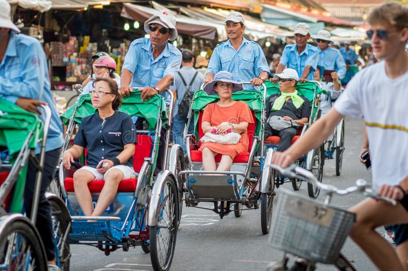 Rickshaws with Asian tourists in Hoi An royalty free stock images