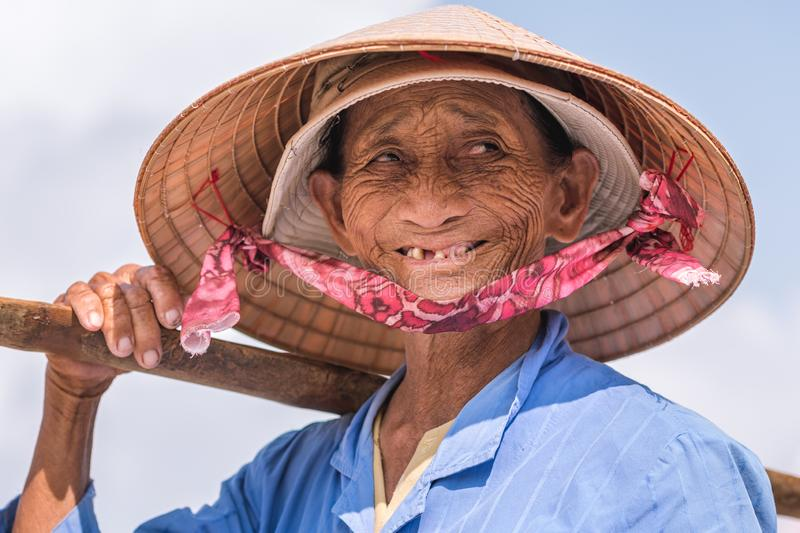 Hoi An, Vietnam: a smiling elderly Vietnamese lady, a street vendor, poses in a conical hat. Hoi An, Vietnam - October 28, 2018: a smiling elderly Vietnamese stock images