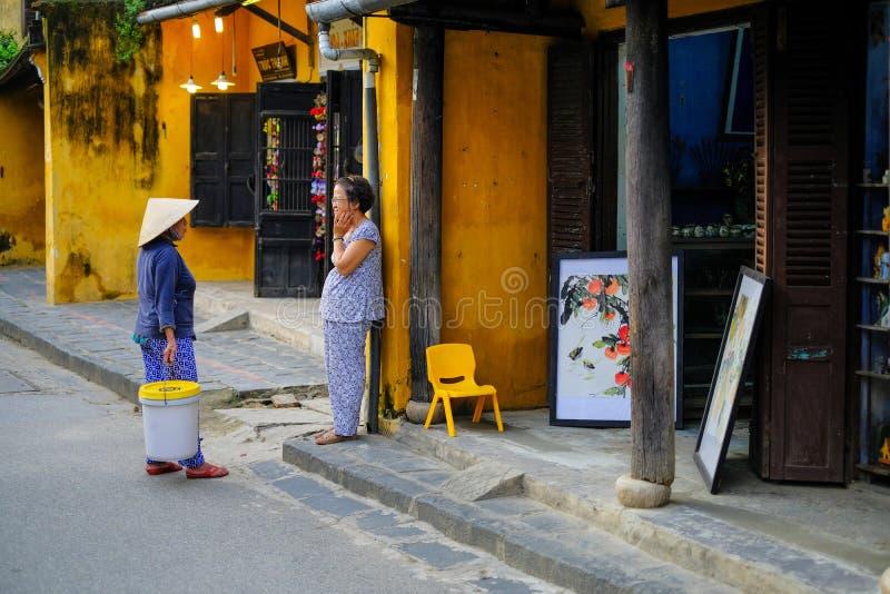 Hoi An/Vietnam, 11/11/2017: Twee lokale Vietnamese vrouwen die zich voor een gele muur in een straatscène bevinden van Hoi An, Vi stock foto