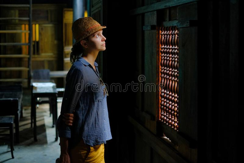 Hoi An/Vietnam, 11/11/2017: Vrouwelijke toerist die zich in het donkere houten binnenland van een traditioneel huis Tan Ky in Hoi stock foto's