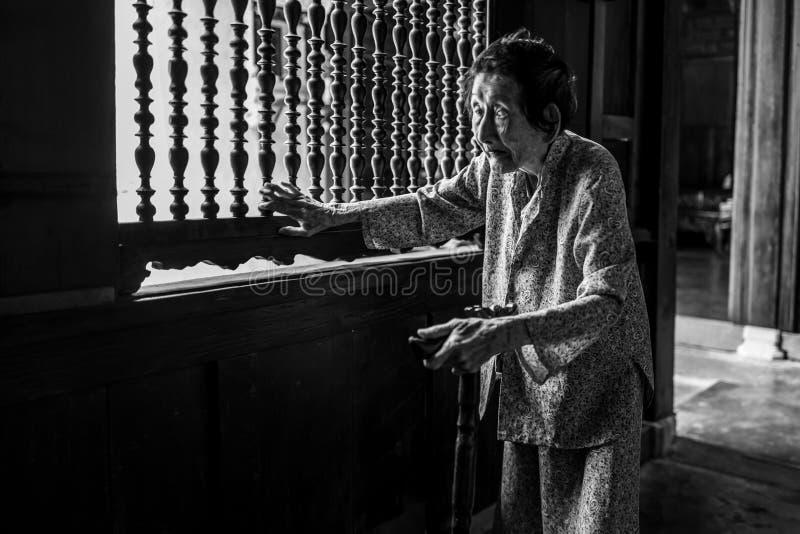 Hoi An, Vietname - 20 de abril de 2018: A mulher idosa anda lentamente casa velha na cidade velha de Hoi An fotografia de stock royalty free