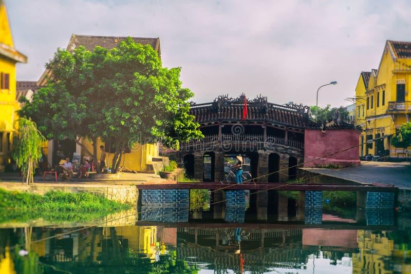 Hoi An, Vietname - 2 de setembro de 2013: A mulher está andando com sua bicicleta sobre a ponte fotografia de stock royalty free