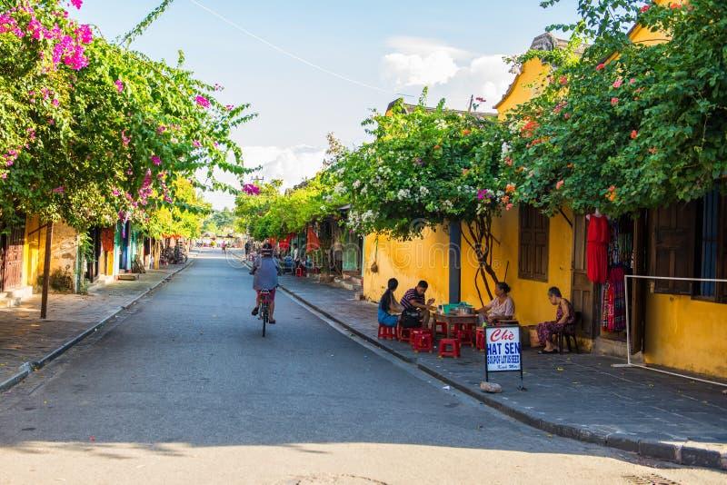 Hoi An, Vietname - 2 de setembro de 2013: O homem está conduzindo uma bicicleta na rua fotos de stock royalty free