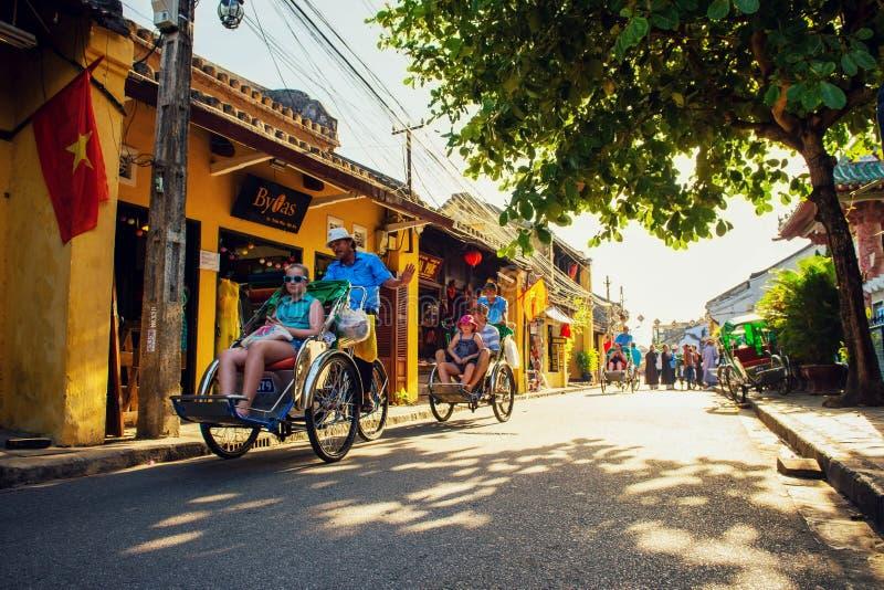 Hoi An, Vietname - 2 de setembro de 2013: Os turistas estão circundando na rua por cyclos fotos de stock