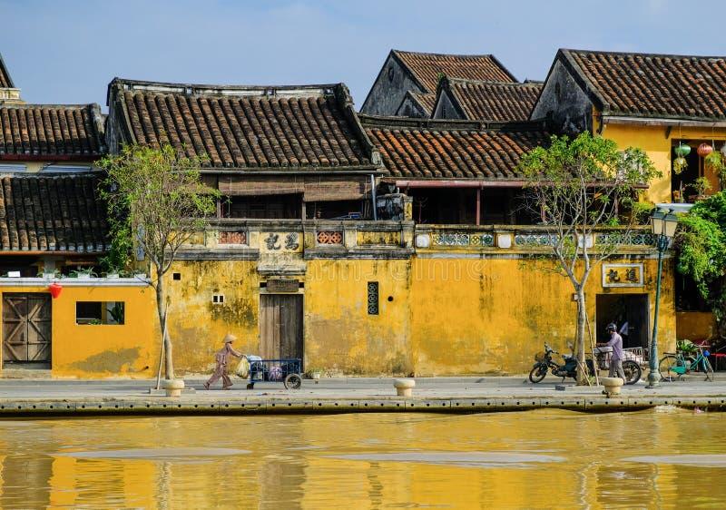 Hoi An/Vietname, 12/11/2017: Mulher vietnamiana local com o chapéu do arroz que empurra um transporte na frente das casas tradici imagem de stock royalty free