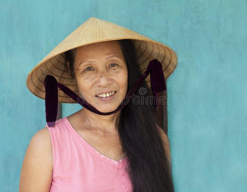Hoi, WIETNAM, Lipiec 2017: zbliżenie twarzy portret jest ubranym conical kapelusz wietnamczyk kobieta zdjęcie royalty free