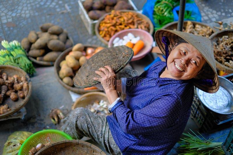 Hoi Wietnam/, 12/11/2017: Lokalna wietnamczyk kobieta uśmiecha się warzywa na tradycyjnym ulicznym rynku w Hoi i sprzedaje, obrazy royalty free
