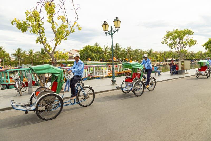 Hoian, Vietnam - 25 DE JUNHO DE 2019 : Taxi tricycle park em Hoi, um velho turista de serviço urbano de bicicleta em volta da cid fotografia de stock royalty free
