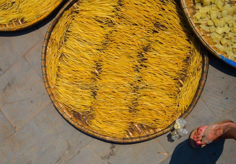 HOIAN, VIETNAM, SEPTIEMBRE, 04 2017: La gente vietnamita seca los tallarines en el sol sobre el pavimento en Hoian en Vietnam foto de archivo