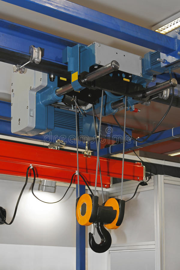 Hoist crane. Overhead crane and hoist device mounted on a trolley at beam royalty free stock photography