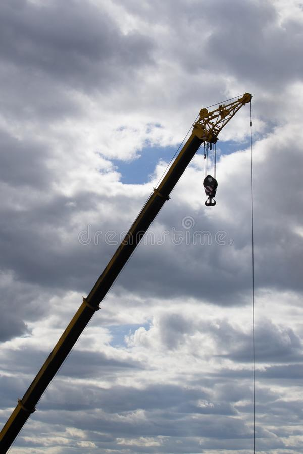 Hoisting crane at a construction site against a cloudy sky stock photo
