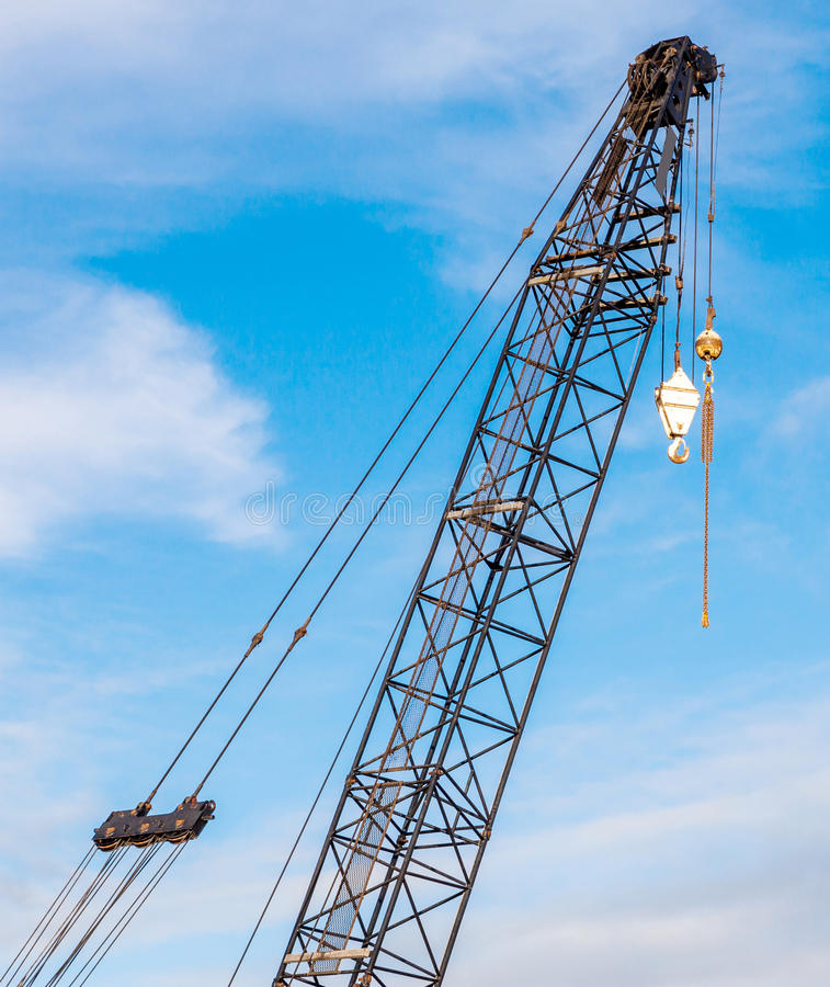 The hoisting crane with pulley and hook in construction site against blue sky background. royalty free stock photo