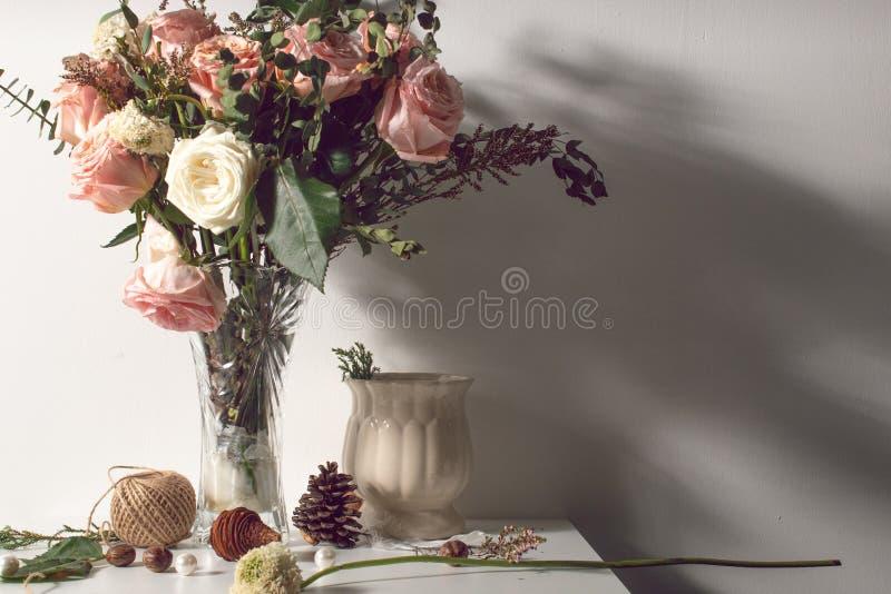 Hoja color de rosa de la flora de la flor con del vintage todavía de la luz vida con el apoyo del florero y de la decoración fotografía de archivo libre de regalías