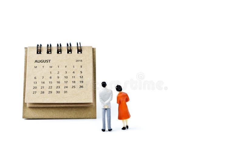 Hoja de August Calendar y hombre y mujer plásticos miniatura en wh fotos de archivo libres de regalías