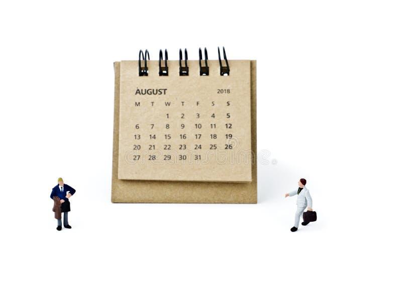 Hoja de August Calendar y hombres de negocios plásticos miniatura en pizca foto de archivo libre de regalías