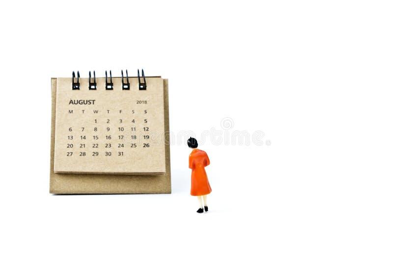 Hoja de August Calendar y mujer plástica miniatura en la parte posterior del blanco imágenes de archivo libres de regalías