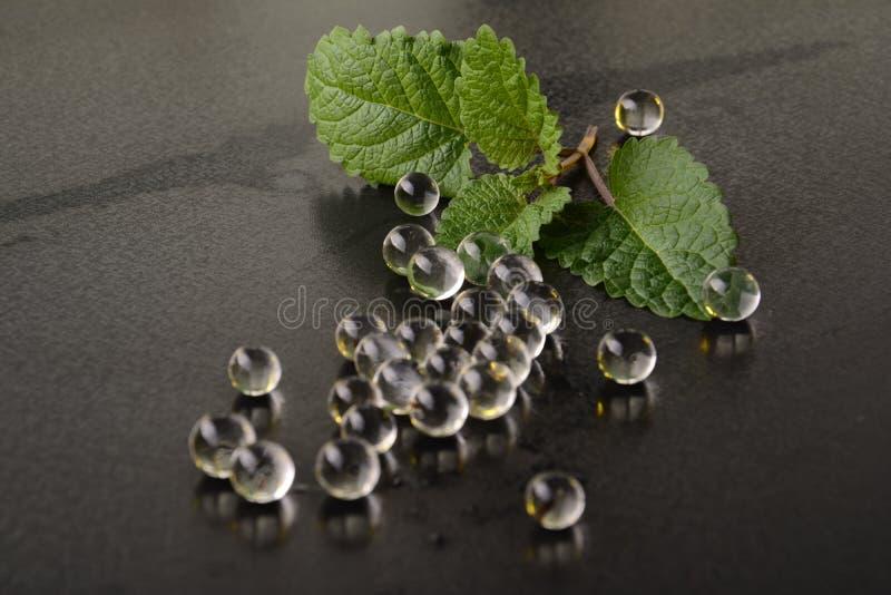 Hoja de la menta fresca en una tabla con las píldoras transparentes de la jalea imágenes de archivo libres de regalías