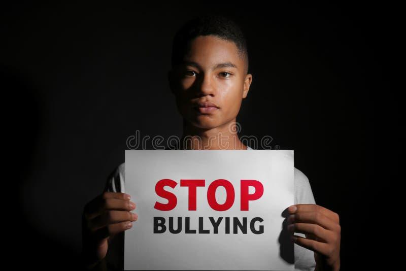 Hoja de papel afroamericana de la tenencia del adolescente con la PARADA del texto QUE TIRANIZA en fondo oscuro fotografía de archivo libre de regalías