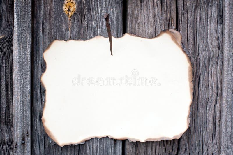 Hoja de papel clavada en la pared de madera fotos de archivo libres de regalías