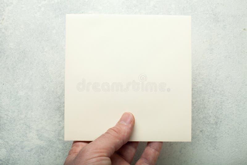 Hoja de papel cuadrada beige en una mano europea, primer Maqueta fotografía de archivo