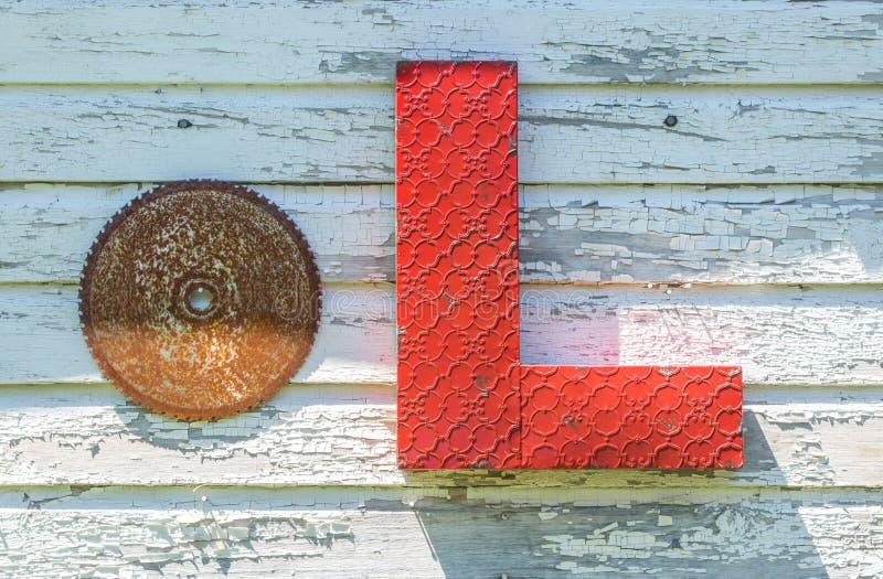 Hoja de sierra y letra aherrumbradas L ejecución de la muestra en una pared exterior foto de archivo