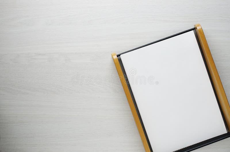Hoja del papel en blanco en el fondo de madera blanco con el espacio de la copia imagenes de archivo