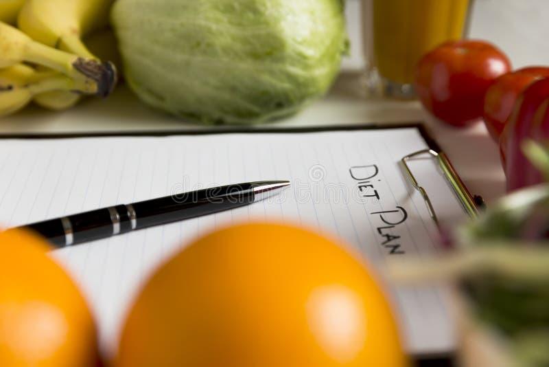 Hoja del plan de la dieta y de productos frescos en la tabla de madera foto de archivo