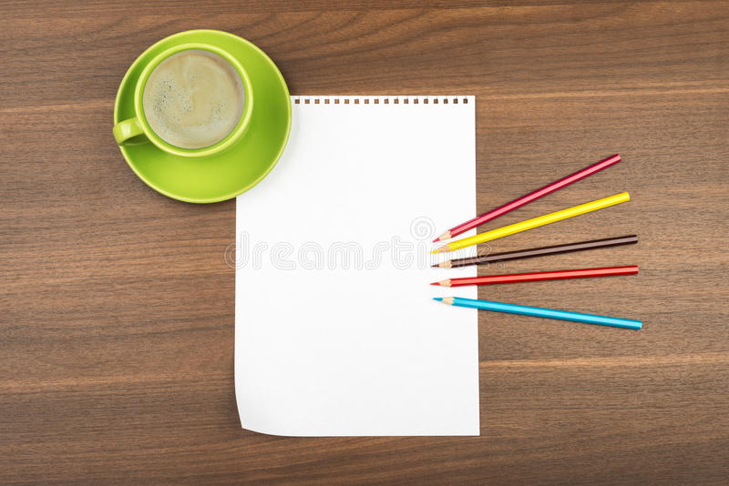 Hoja en blanco de la nota con los creyones y la taza de café fotografía de archivo