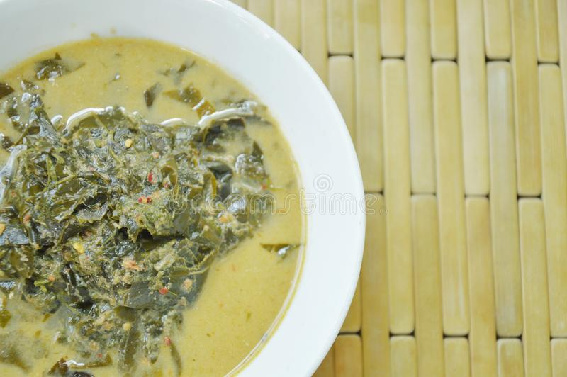 Hoja hervida del árbol de la casia o vaina de cobre tailandesa con leche y curry de coco en el cuenco imágenes de archivo libres de regalías