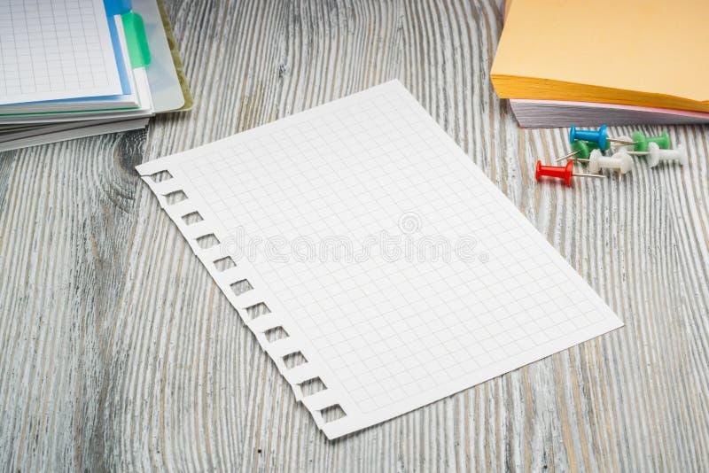 Hoja limpia en célula del cuaderno en la tabla rústica notas foto de archivo libre de regalías