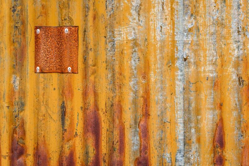 Hoja oxidada de la pared acanalada del metal con los remiendos del metal, como fondo texturizado anaranjado imágenes de archivo libres de regalías