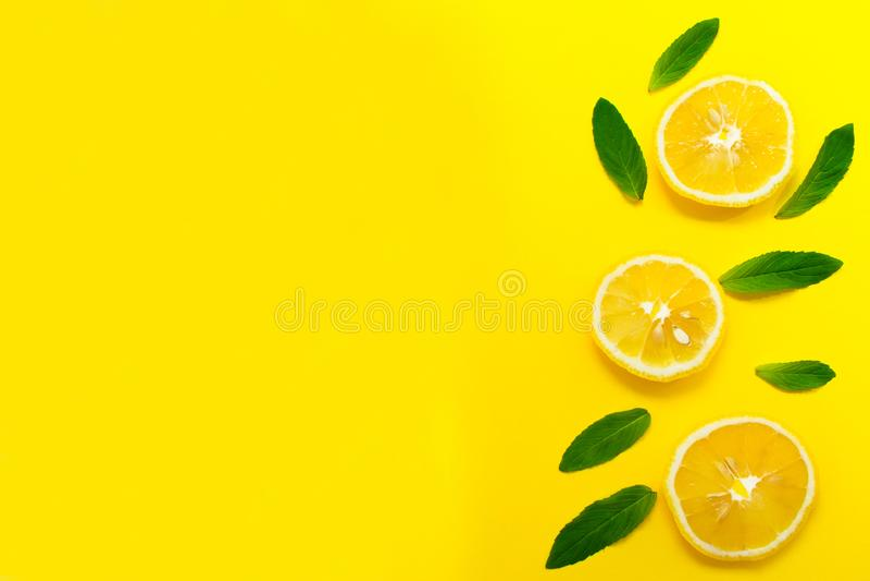 Hojas cortadas del limón y de menta en un fondo amarillo brillante Fondo para el diseño de banderas, blogs Copie el espacio foto de archivo