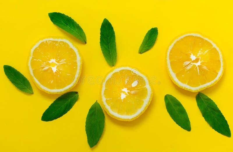 Hojas cortadas del limón y de menta en un fondo amarillo brillante Fondo para el diseño de banderas, páginas web imagen de archivo libre de regalías