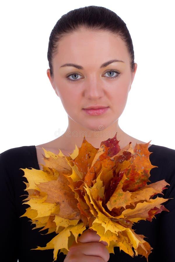 Hojas de arce de la naranja del otoño de la explotación agrícola de la muchacha foto de archivo