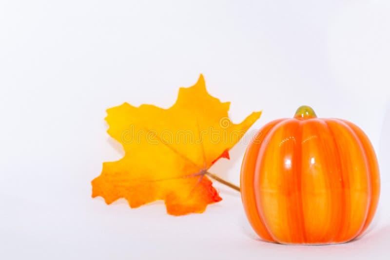 Hojas de arce festivas de color naranja y amarillo y adornos de calabaza en un fondo blanco aislado para dar acción de gracias y foto de archivo