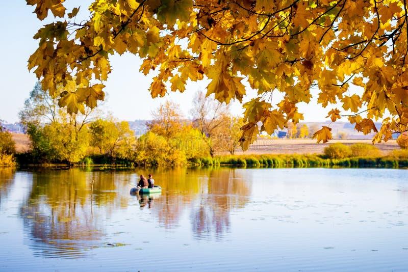 Hojas de arce de oro sobre el río en la caída Pescadores en un barco en el river_ fotos de archivo libres de regalías