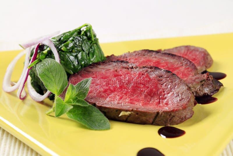Hojas de la carne de vaca y de la espinaca de carne asada foto de archivo