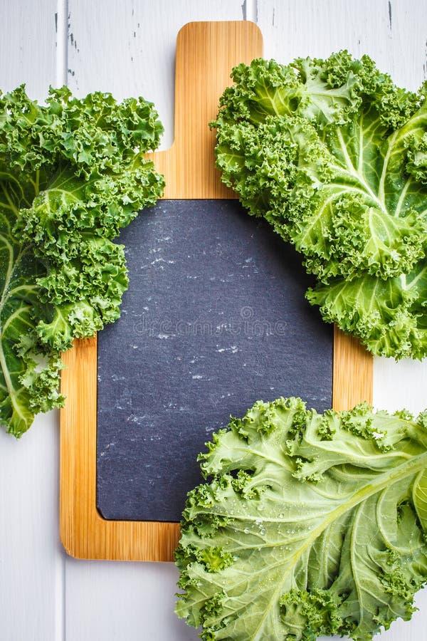 Hojas de la col rizada de la ensalada verde en el tablero de madera blanco del fondo y de la pizarra para el texto, espacio de la foto de archivo