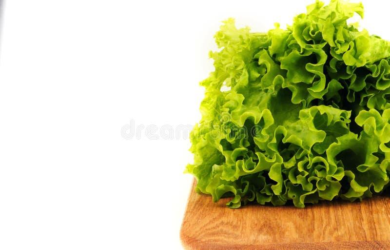 hojas de la ensalada verde en un tablero de madera en un fondo blanco imagen de archivo