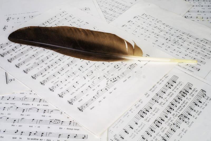 Hojas de la pluma y de música fotos de archivo